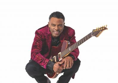 African-American man in black slacks and burgundy jacket holding a guitar