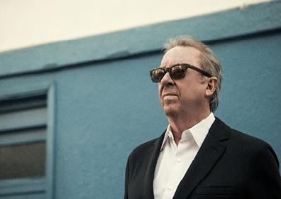 man standing with sunglasses on in front of a blue wall