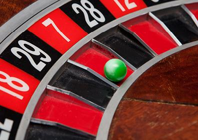 Green Ball Sitting in the Red Number Seven Slot on a Roulette Table