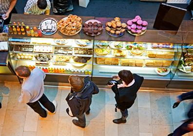 A Line of People in Front of Glass Covered Display of a Variety of Baked Goods