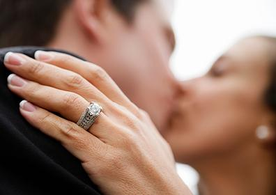 woman and man kissing and her showing her wedding ring up front