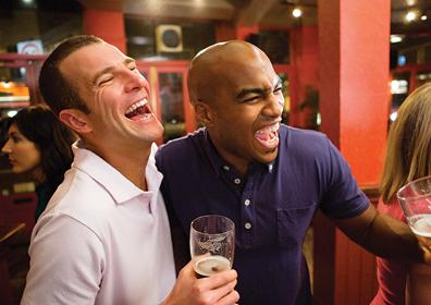 men laughing next to each other with a beer in their hand