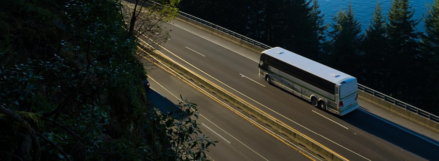 Aerial Shot of a Bus Driving on a Bridge Over Forest by a Body of Water