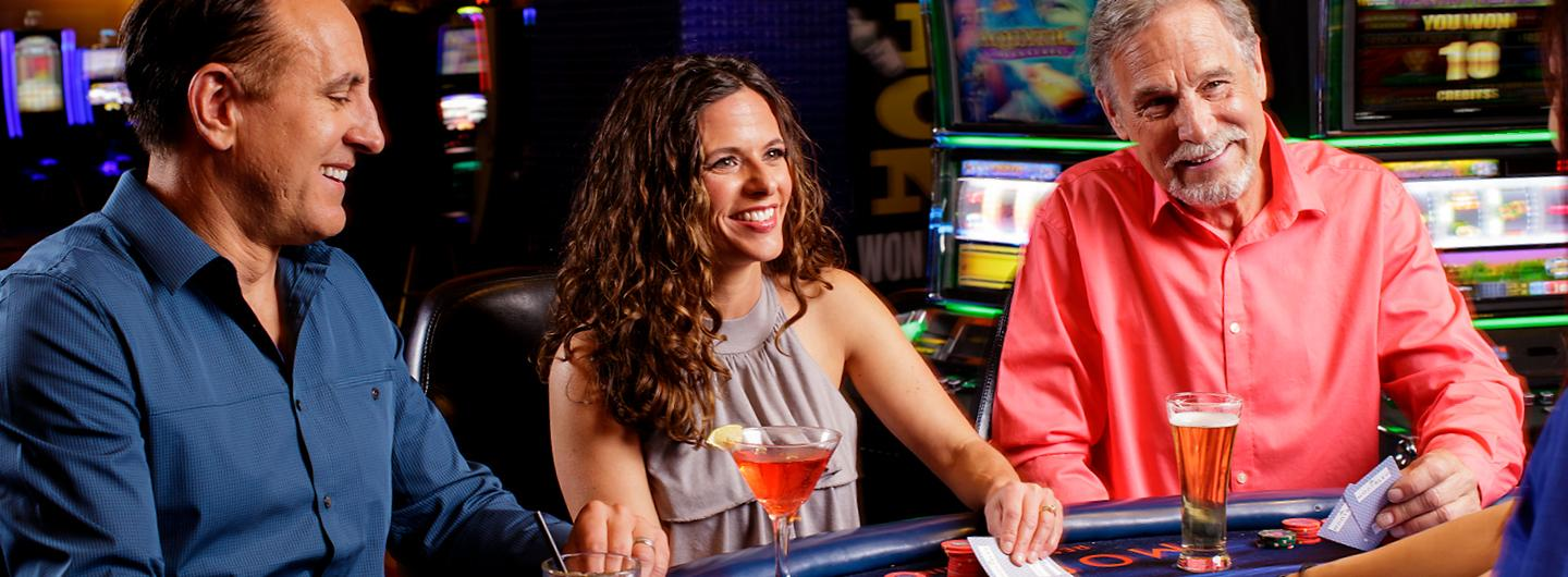 Two Men and One Woman Smiling at a Card Table