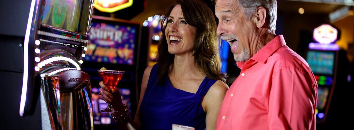 Man and Woman Celebrating a Win in Front of a Slot Machine