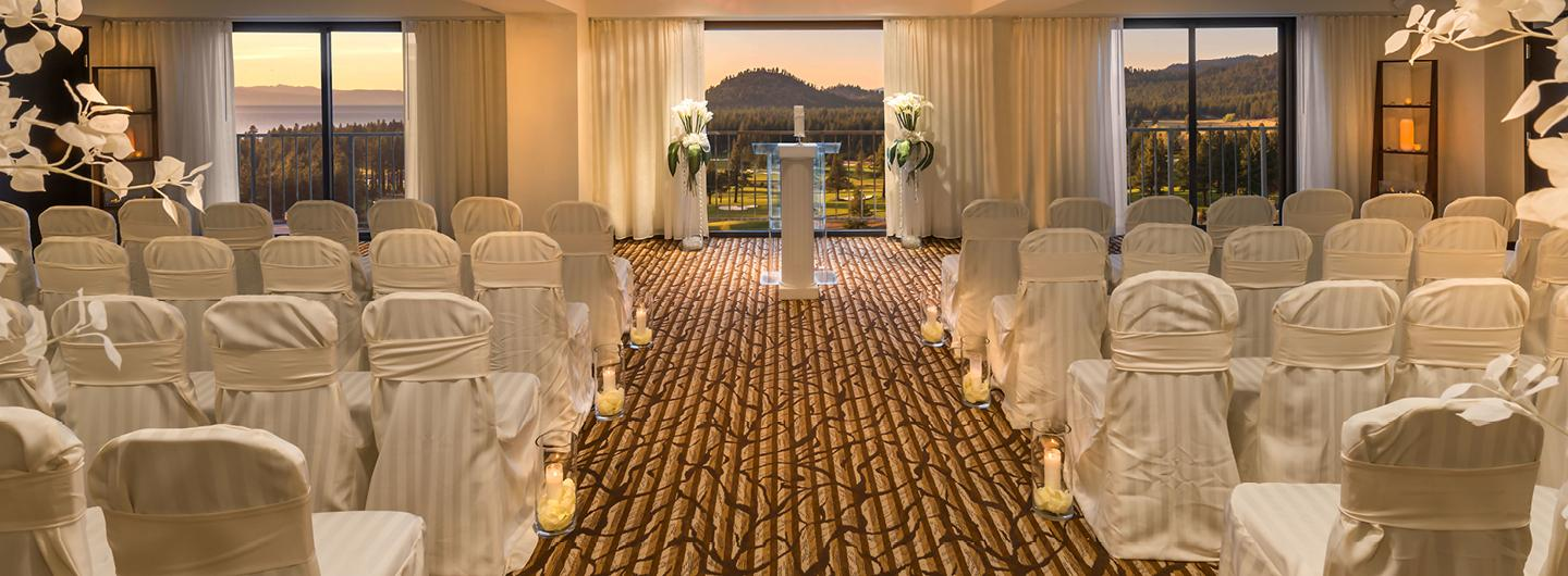 A Gold Room with White Furniture all Facing a White Pillar and Glass Podium Behind which is a Beautiful View of Rolling Hills
