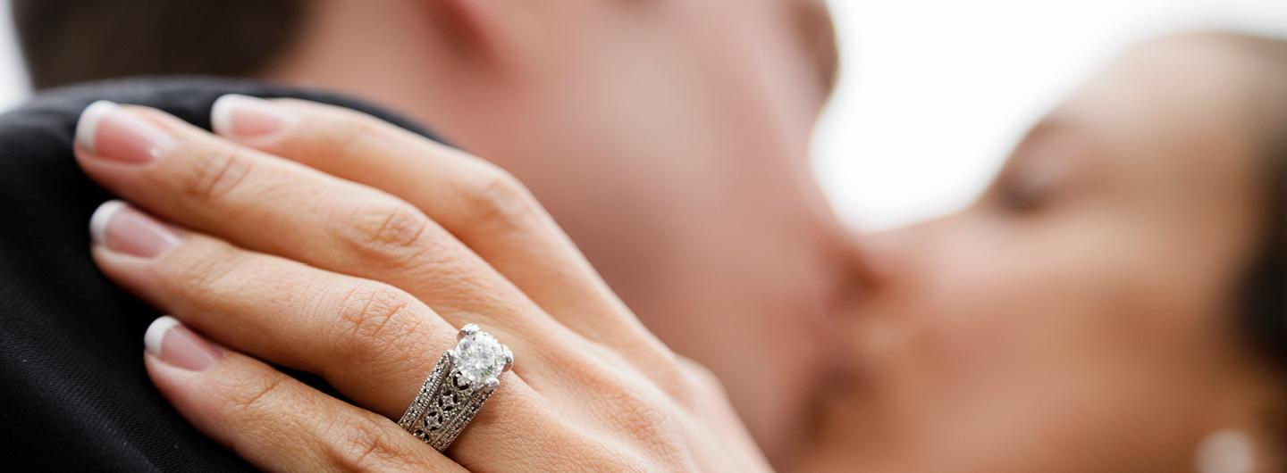 A Closeup of a Bride's Wedding Wring on Her Hand that is Resting on the Shoulder of the Groom Who She is Kissing