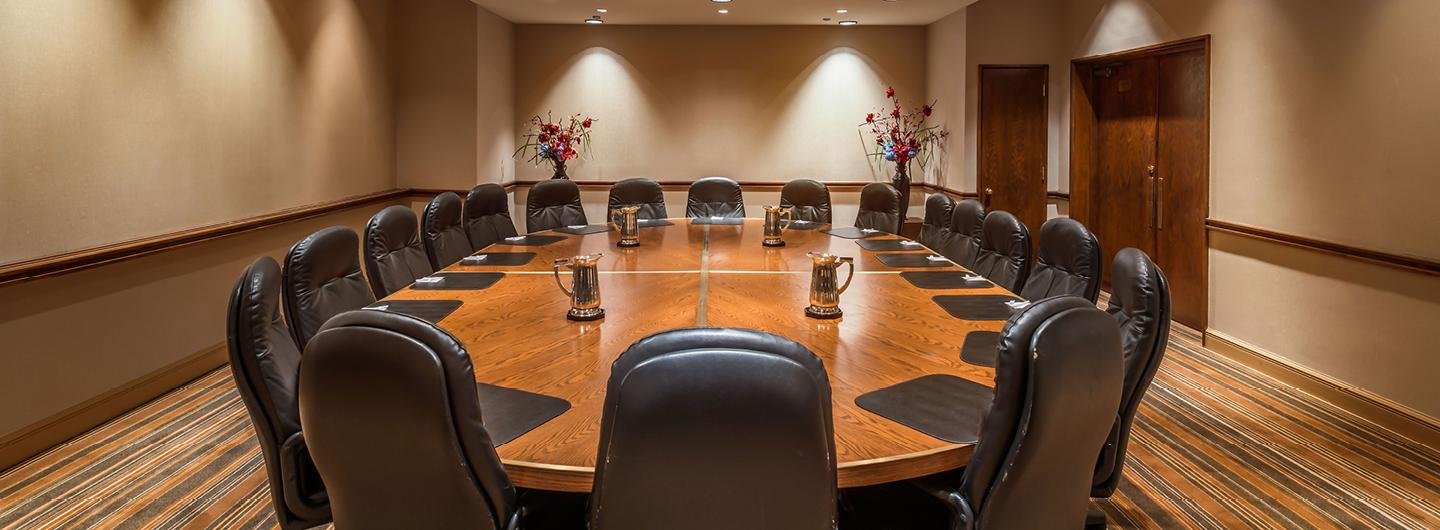 Large Finished Wood Table with a Dozen Black Chairs