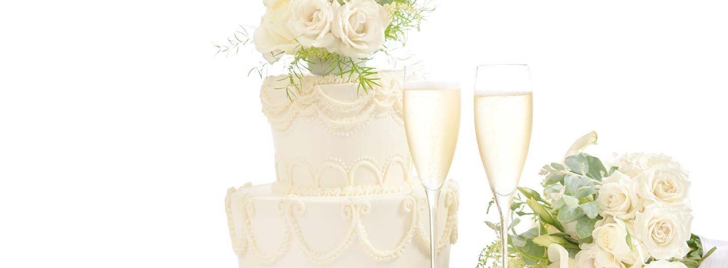 A Highly Saturated White Photo of a White Wedding Cake with White Wine and Bouquet