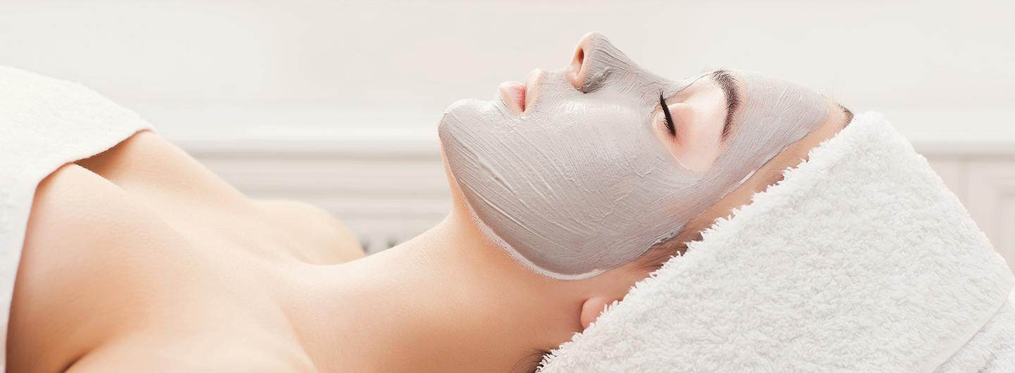 woman laying down with a clay mask on face