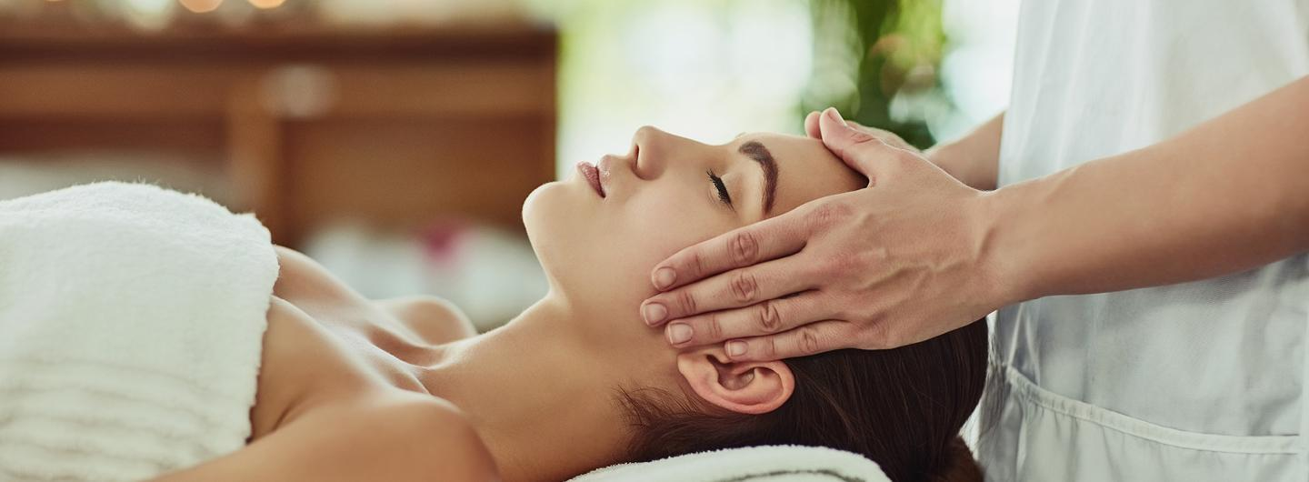 woman laying down getting her temples massaged