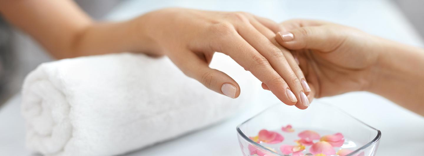 a woman's hand getting held above a bowl of water with flower petals