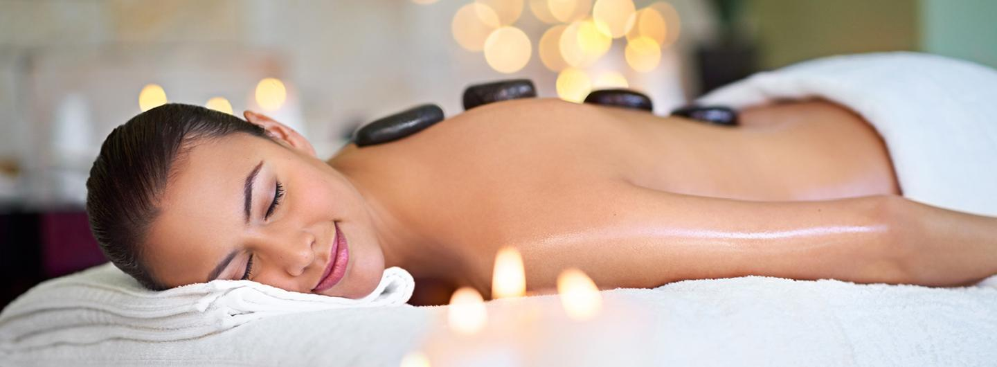 woman lying down with hot stones on her back surrounded by candles