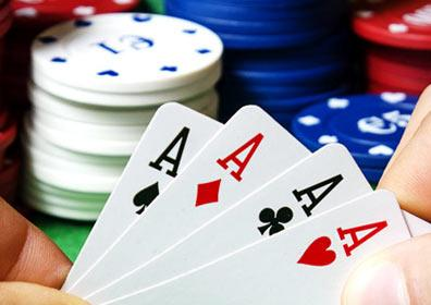 A person playing poker with a hand of four aces and a stack of chips