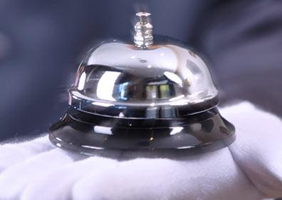 chrome bell in white gloved hand
