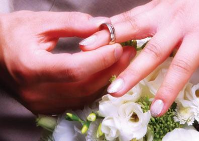 A man placing a wedding ring on a woman