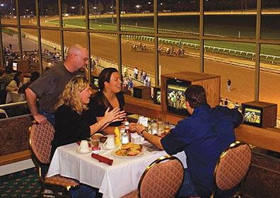 A group of people dining at the Mountaineer Club and watching a live horse race