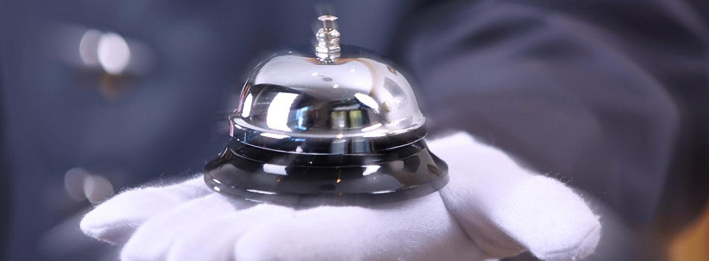 chrome bell in white gloved hand