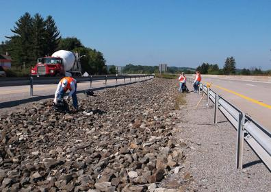 people cleaning up on the side of the highway