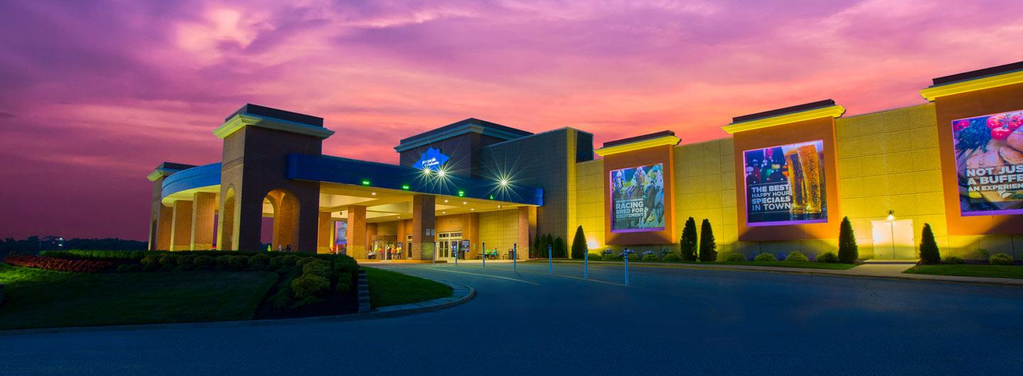 Exterior view of Presque Isle Downs & Casino with the sun setting behind it