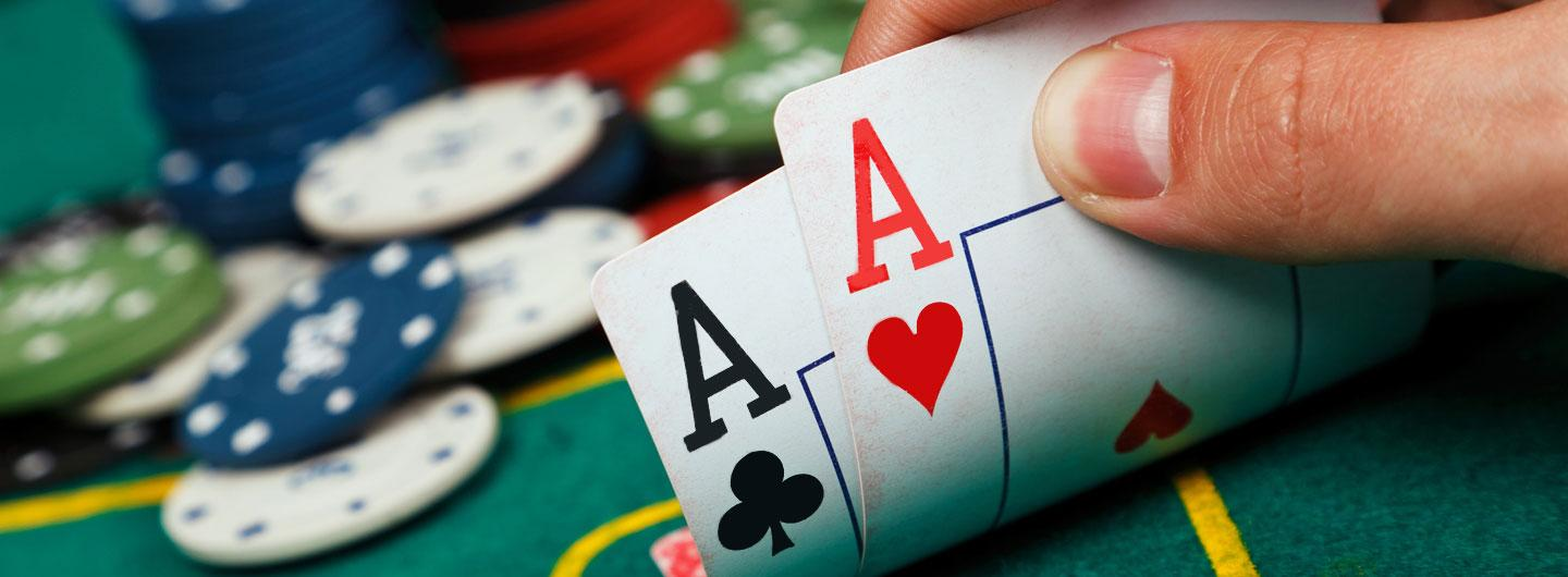 Two cards that are aces with a stack of chips