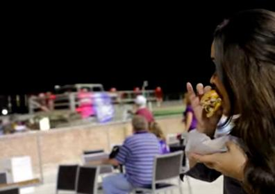 A girl eating a menu item at Pompano Park from The Lone Wolf Food Truck