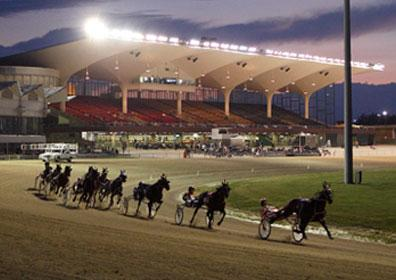 A live harness horse race going into a turn with the sun setting behind the stands