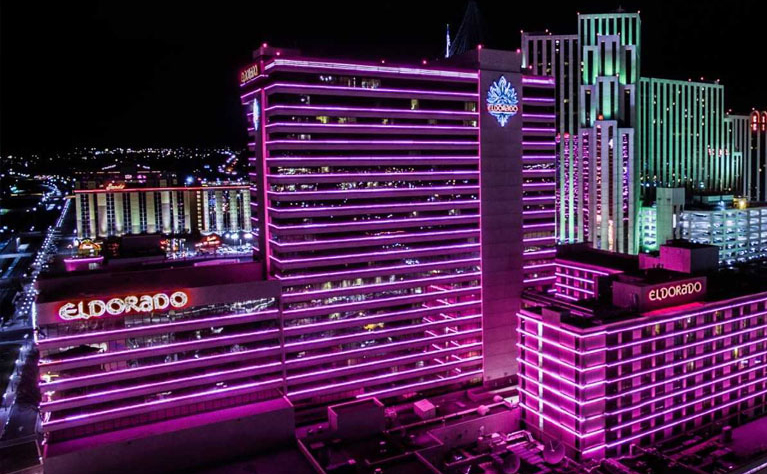 Aerial Picture of the outside building of The Eldorado Resort and Casino at night, illuminated by pink neon with the Silver Legacy in the background of the picture