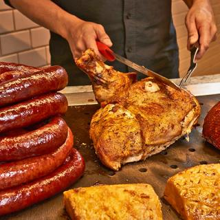 carving station with sausage and turkey and ham