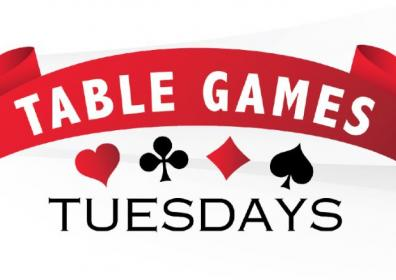 Table games tuesday text with red ribbon