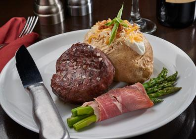 Filet Mignon served with prosciutto wrapped asparagus and a loaded baked potato