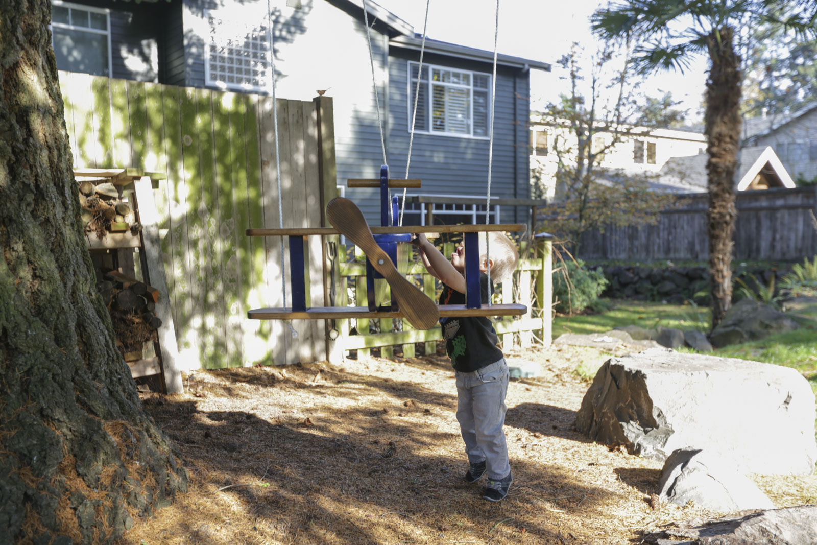 kid playing with wooden airplane swing