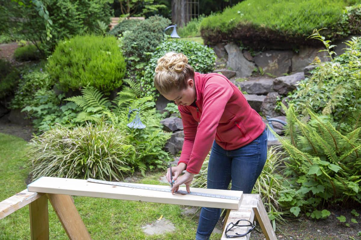 measuring to cut wood in backyard