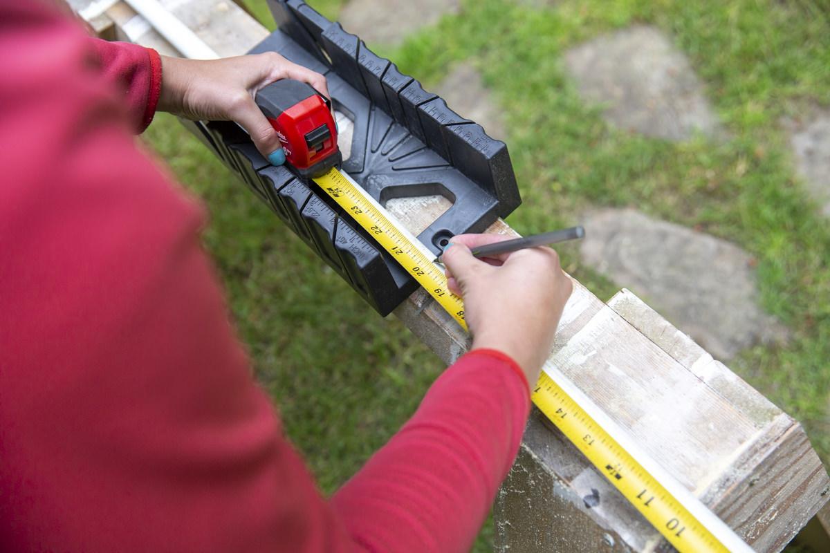 measuring to cut wood for slip n slide