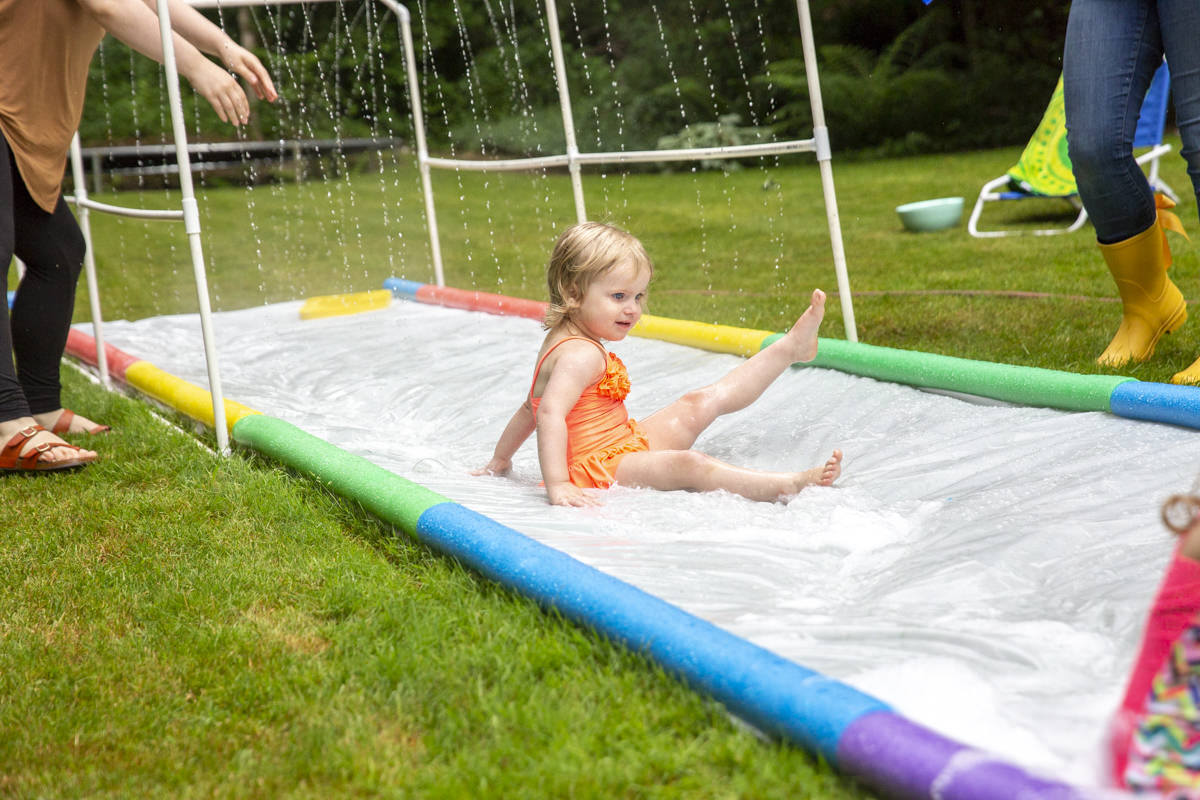 child sliding on slip and slide