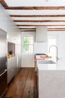 An Ad Copywriter Edits His Manhattan Row House—and Finds a New Calling - Photo 4 of 14 - The 12-foot kitchen island, topped in polished Carrara marble, has a waterfall edge and an integrated apron sink made from the same stone slab.