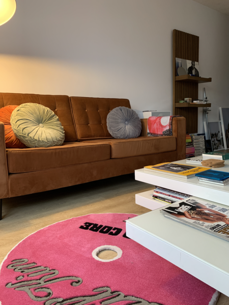 A CD rug celebrating Lil Kim's debut album Hard Core pairs with a gold velour couch in the living room.