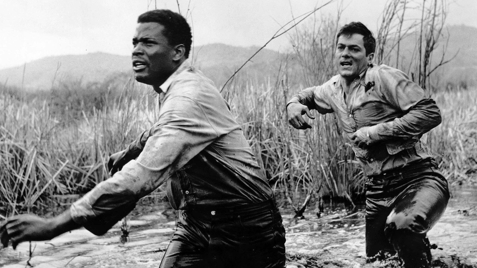 Sidney Poitier and Tony Curtis are on the run in	<em>The Defiant Ones</em>