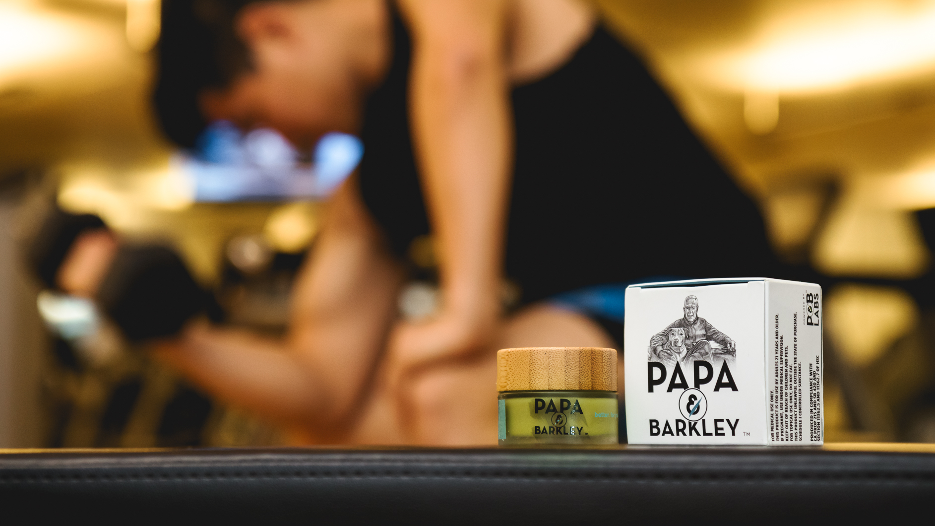 Close up image of Papa & Barkely Releaf Balm with a man lifting weights in the background.