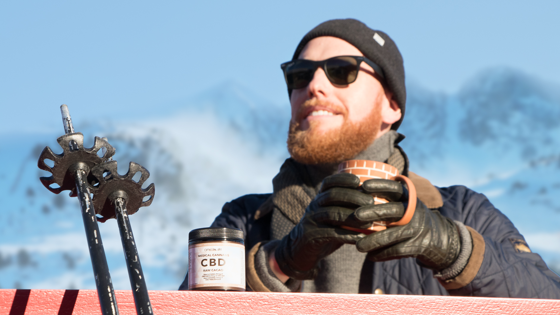 Image of a man at a ski resort enjoying a mug of cannabis-infused hot chocolate.