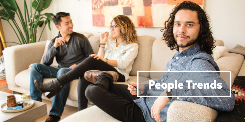 Image of 3 people sitting in a living room using marijuana vaporizers. 1 in 3 is female.