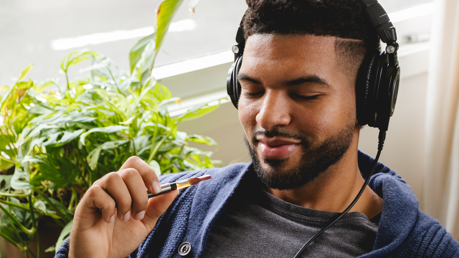 Image of a man listening to music through his headphones and holding a marijuana vaporizer