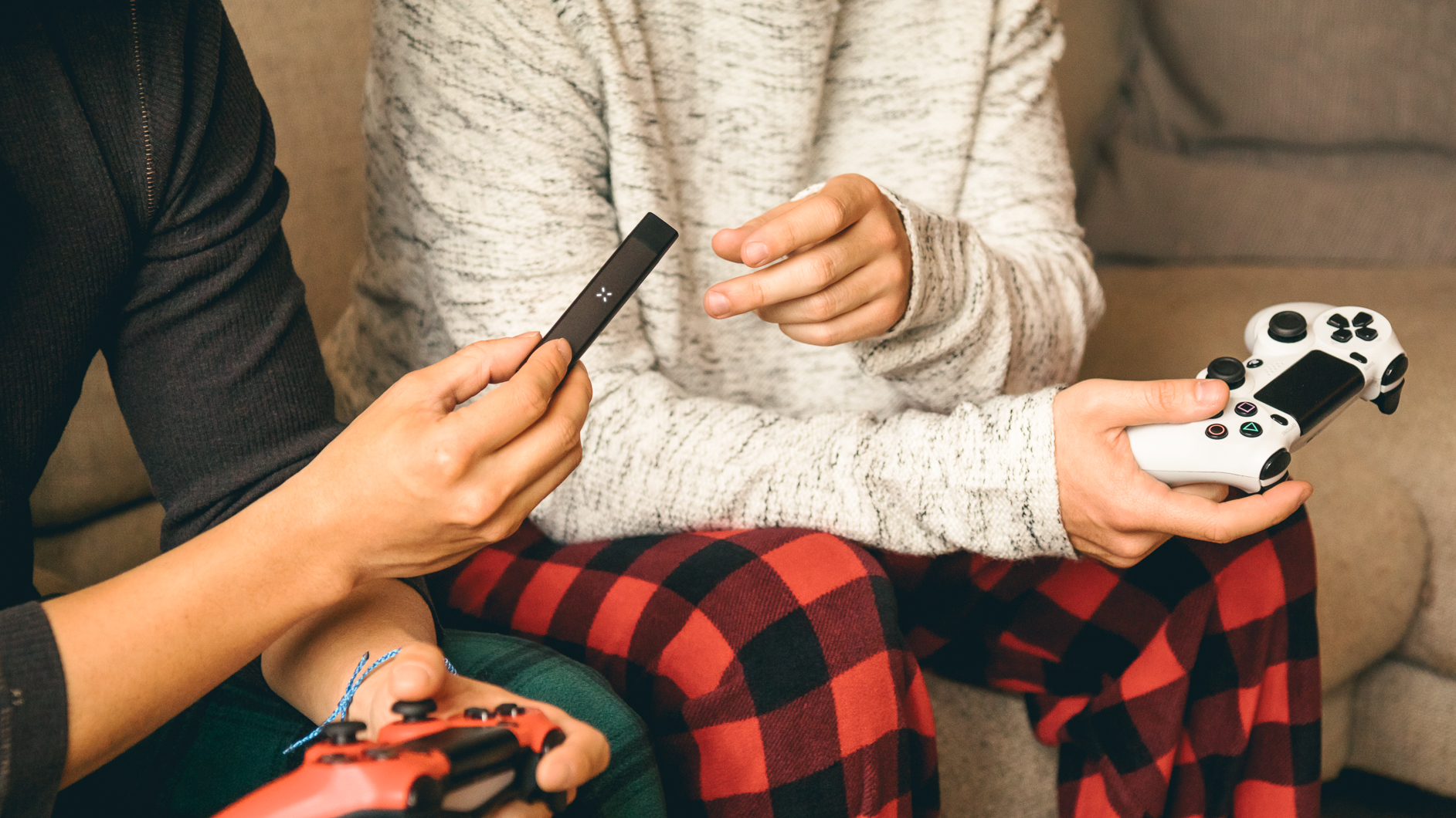 Image of two guys sharing a PAX Era marijuana vaporizer as they sit on the couch playing video games.
