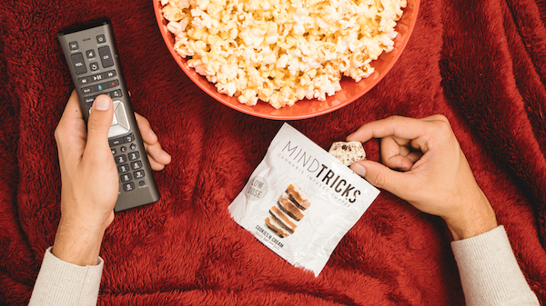 Image of someone holding a remote control with popcorn and edible marijuana treats by Jetty.