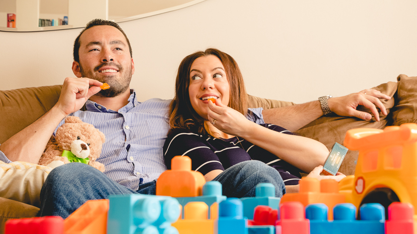 Image of parents relaxing on the couch enjoying edible marijuana gummies