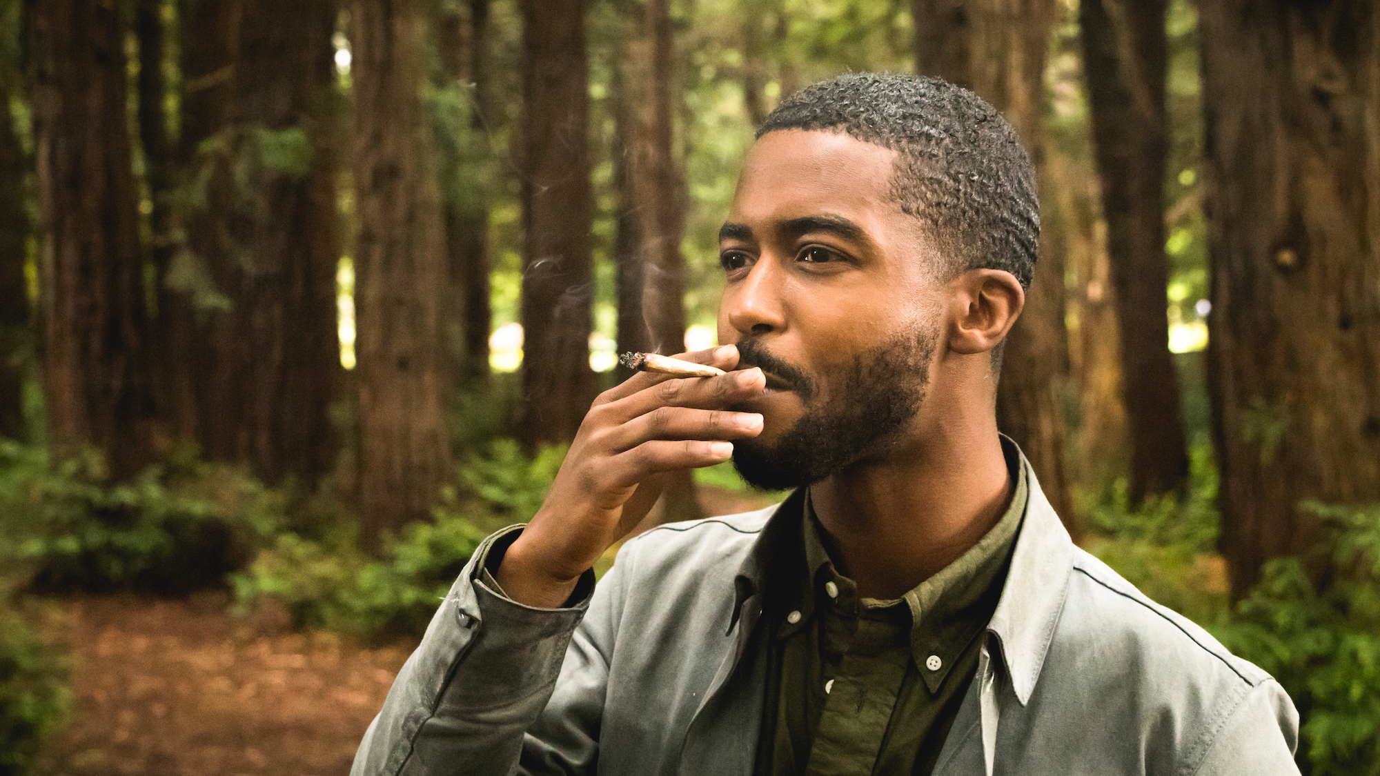 Image of a man in the woods enjoying nature and his marijuana preroll