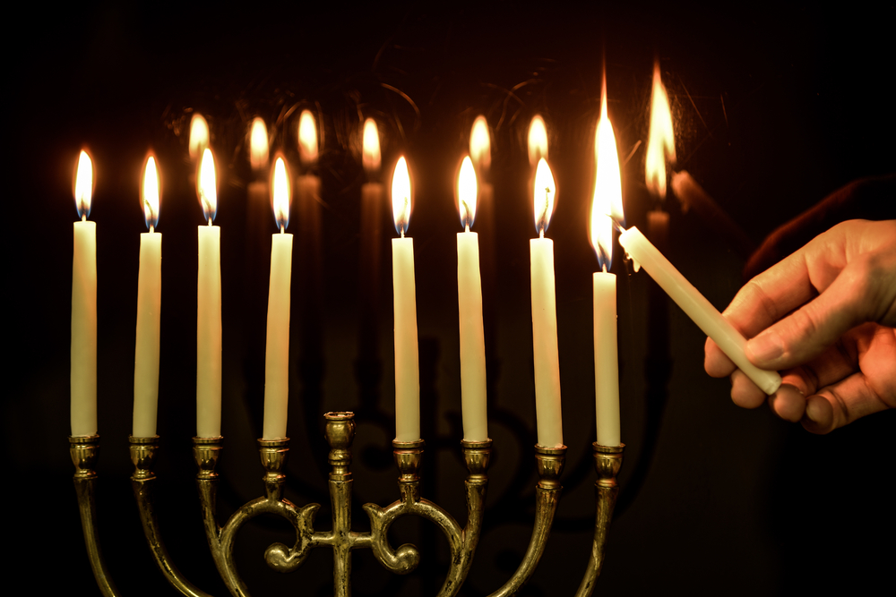 Image of someone lighting up a menorah