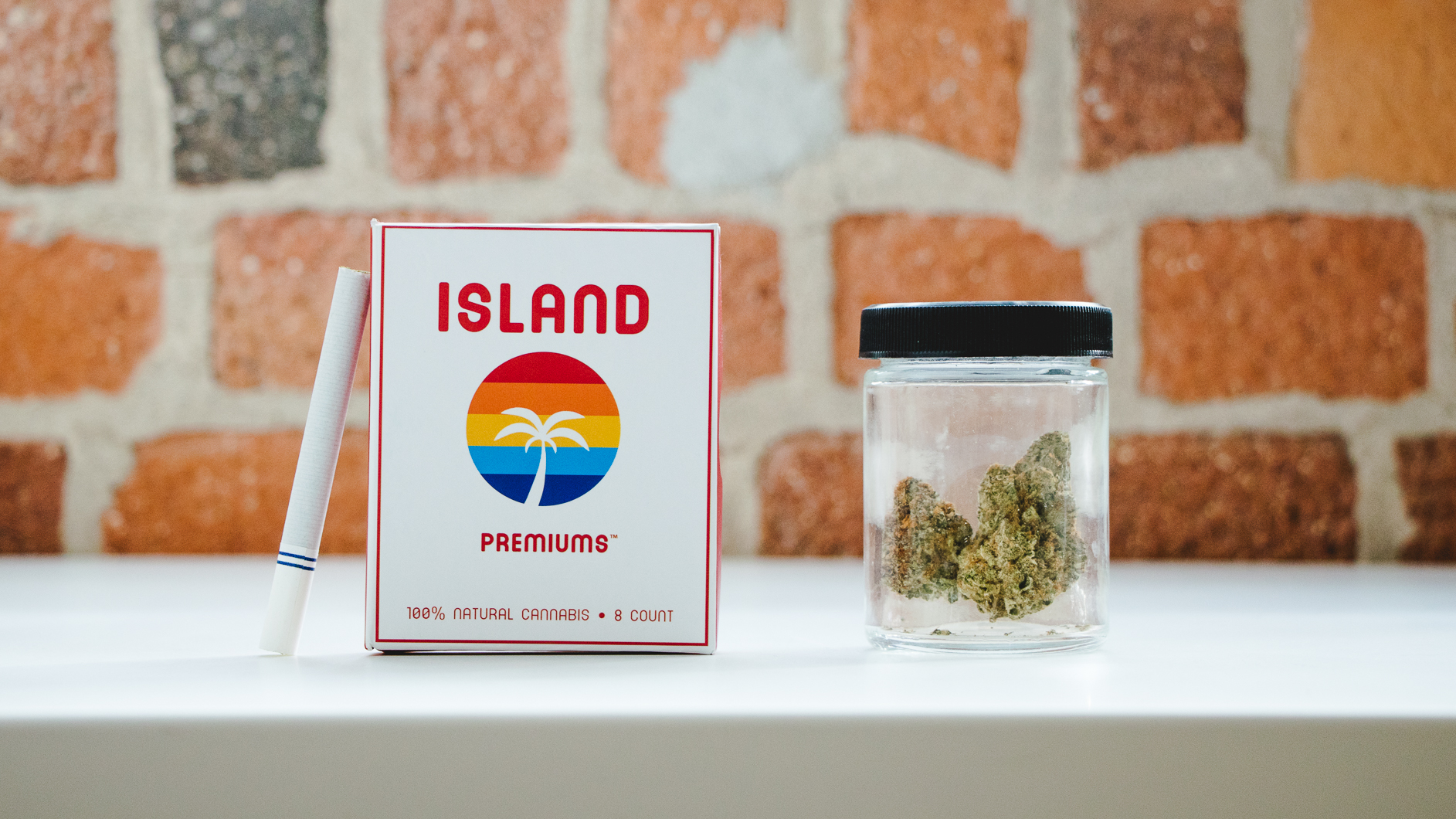 Image of a pack of marijuana prerolls next to a jar of flower