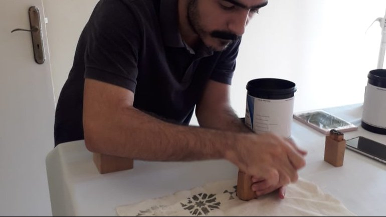 This is me making a print using a geometric design that I carved on wood.