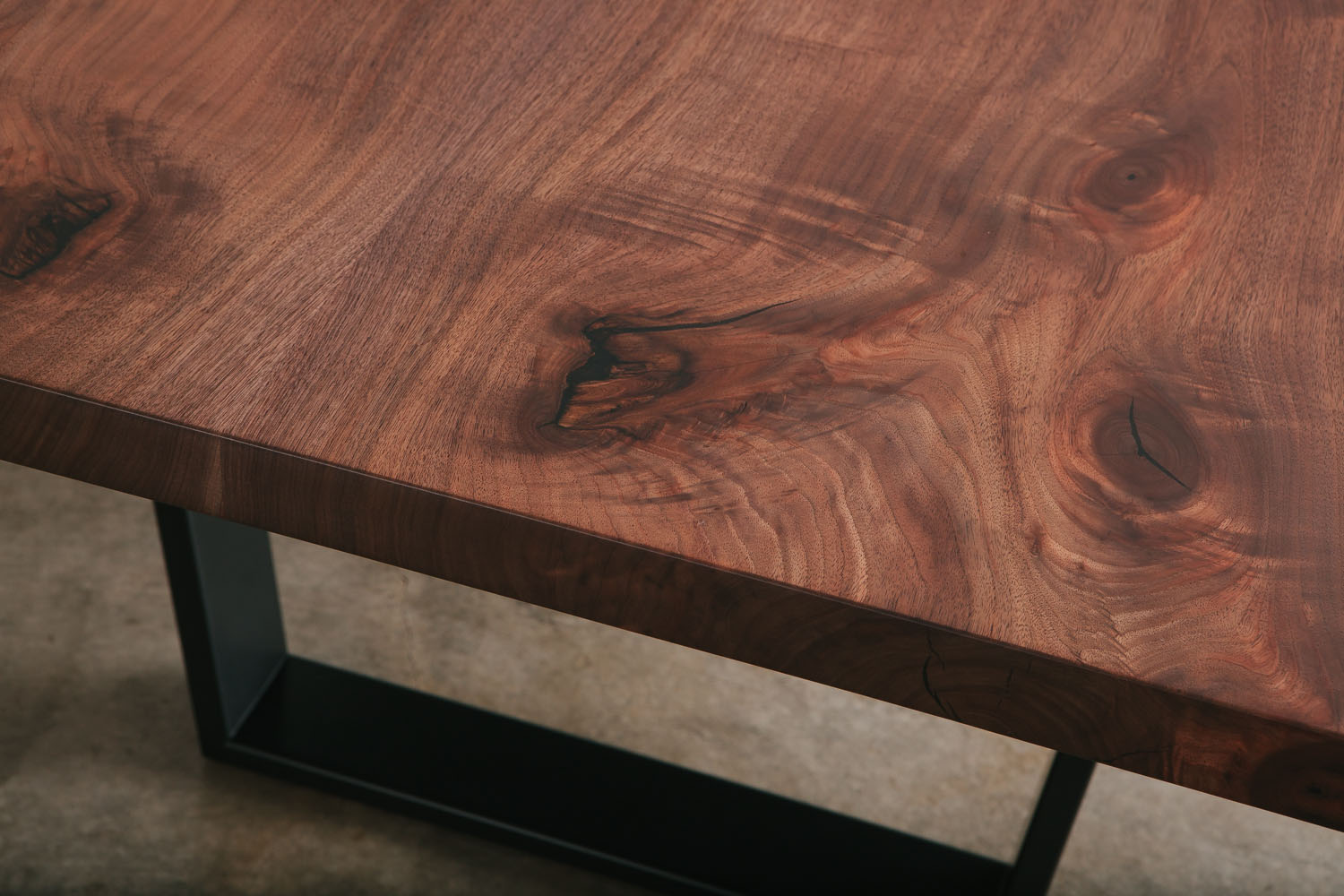 Modern walnut dining table with figured grain and natural tree knot